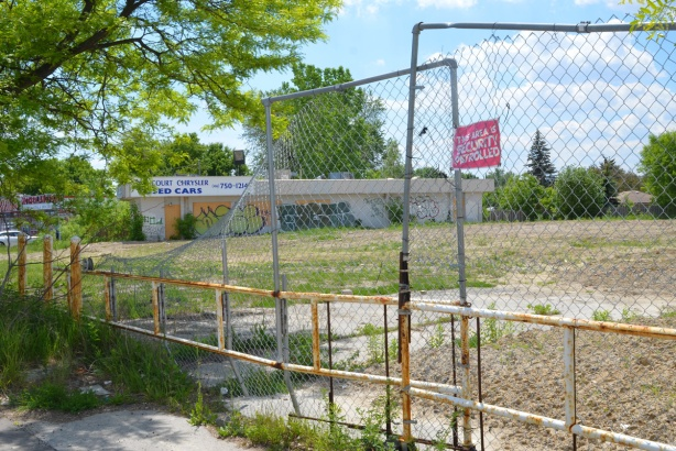 yellow gate and construction fence around a vacant lot with a building in the far corner, Agincourt Used cars, closed business, graffiti on building,