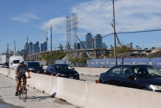 construction zone along Villiers Street, concrete barricades separating car traffic from cyclists, blue fence around construction, demolition of the Gardiner Expressway, skyline in background
