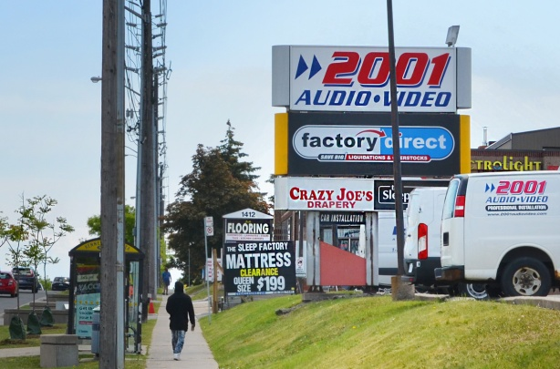 a person walks past stores with large signs in front of them, 2001 Audio and Video, Crazy Joes Drapery, Sleep Factory mattress, and a flooring store