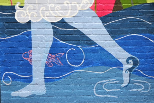 part of mural, pale blue legs and bare feet walking in swirling water