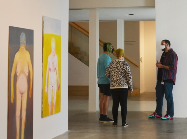 three people talking in a gallery with two large paintings of full frontal naked women on one of the walls