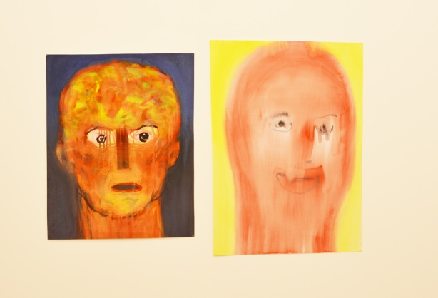 two paintings of faces on a gallery wall