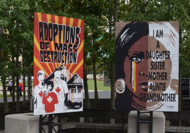 2 posters, adoption of mass destruction, and I am a mother sister auntie grandmother, protest signs on indigenous rights and past Canadian history of abuses