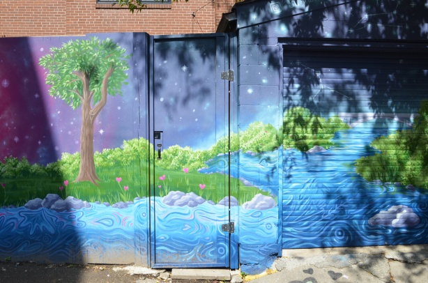 part of a mural in an alley covers fence and a door in the fence, wood, painting of a landscape scene with water, green shrubs, a tree, and night sky with stars