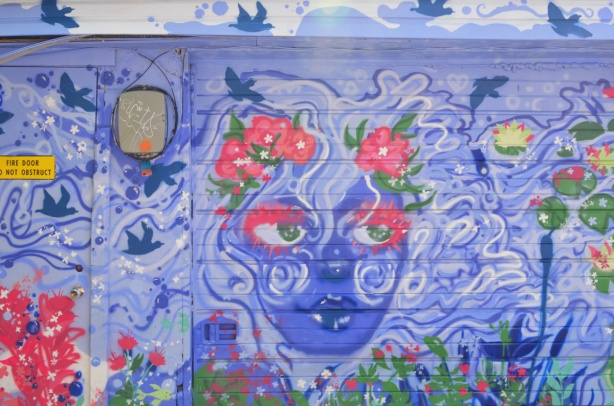 on a garage door in an alley, a mural of a blue faced women with swirly white and blue hair, flowers in her hair
