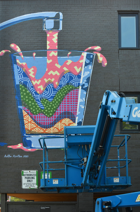 lift truck beside wall with new mural of a glass of water in many colours and patterns,
