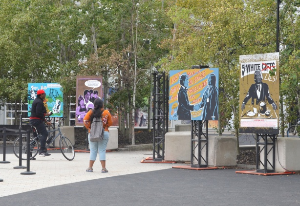 a man on a bike and a woman with a large backpack standing in front of posters by Jay Soule on display outside at Harbourfront, Indigenous Rights, history of abuse, protest,