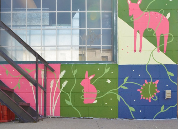 part of a mural by Merryn about invasive species in the Don Valley, a pink rabbit and a pink deer having to contend with out of control greenery