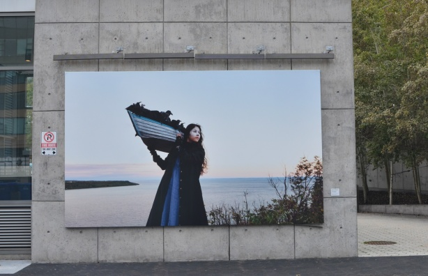 woman holding a small boat on her shoulders, lake in the background, large photograph by Meryl McMaster on display at Canada Square at Harbourfont