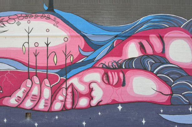 part of a mural by Mo Thunder on Broadview Ave of a mother and child lying in water, child has plants in her hand, mother earth theme, water theme