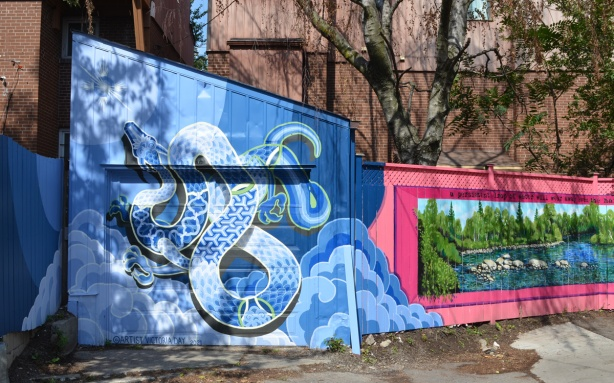 two murals in a Toronto alley, on the left, all in blue tones, a water serpent, very big and rising out of the water. on the right, a long horizontal lake scene with a pink border