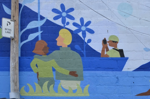 part of a mural, a couple standing by a lake with arms around each other, seen from the back
