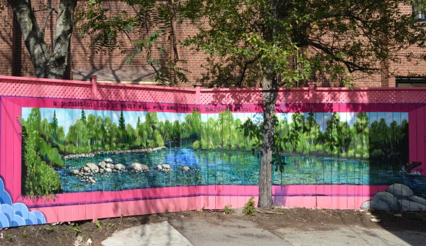 on a wood fence in an alley, a lake scene mural with pink border