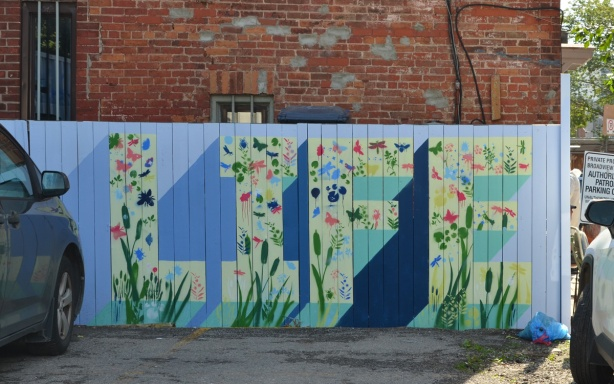 the word life painted on a fence white letters on blue background with small flowers painted all over it.