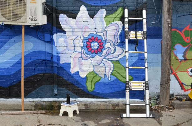 large white flower painted in a mural, on a blue watery background, ladder sitting in front of it, step stool with a can of spray paint