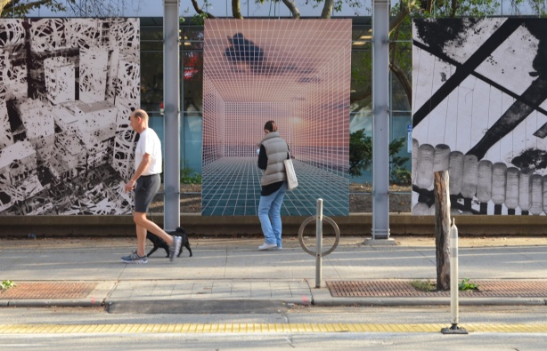 a woman stops to take a picture of a large photo on display on King Street West while a man and his black dog keep walking past the photos