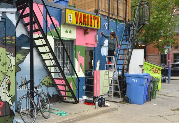 metal stair cases, exterior of a variety store, laneway, bike, garbage bins, artist on a ladder painting a mural