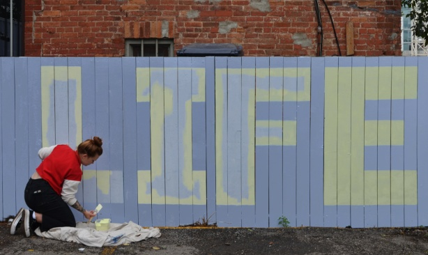 the word life painted on a fence white letters on blue background