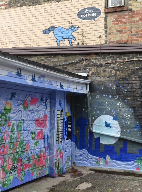 murals in a lane in Riverside near Queen and Broadview, Toronto. raccoon on upper story approaching a window, night scene on lower floor with bird silhoutted by full moon