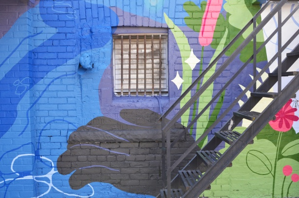 black hand, large painted, mural, at bottom of metal exterior stairs and under a window with metal bars, part of a mural with water and plants